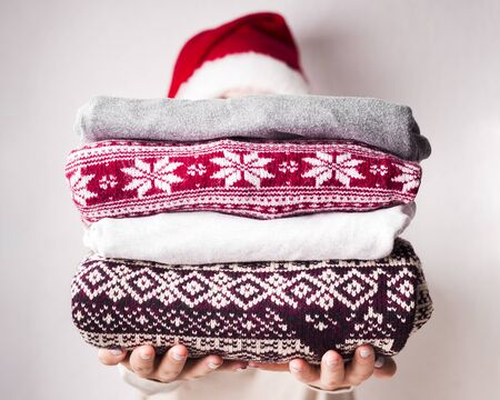 Christmas sales. Woman holding winter sweaters with patterns on background