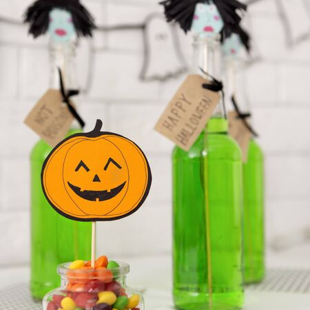 Sweet halloween. Trick or treat candies and green cocktails in bottles over loft style background
