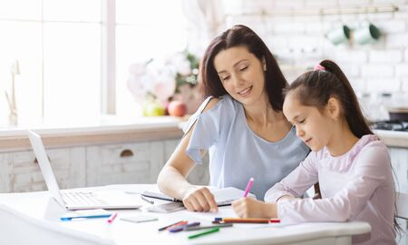 Education concept. Caring mother assisting to daughter with her homework, spending time in kitchen at home, panorama