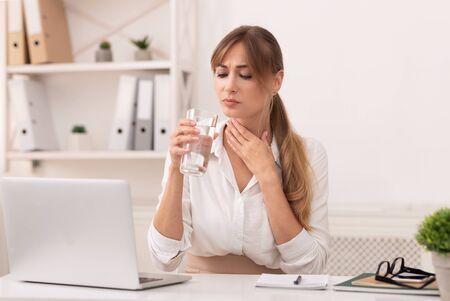 Kranke Geschäftsdame mit Halsschmerzen mit Glas Wasser am Laptop im modernen Büro arbeiten. Selektiver Fokus