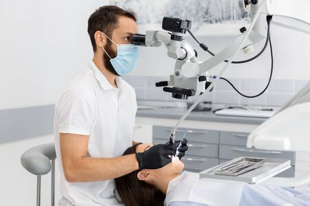 Professional bearded male dentist using modern technologies in dental treatment, complicated cases in stomatology Stockfoto