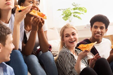 Czas pizzy. Różnorodni przyjaciele jedzący i rozmawiający, spędzający razem czas w domu