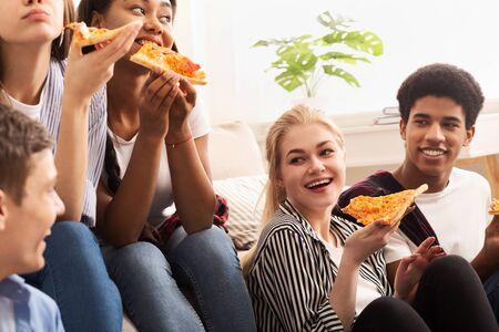 Tempo della pizza. Diversi amici che mangiano e parlano, trascorrono del tempo insieme a casa