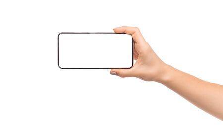 Mano de mujer sosteniendo moderno smartphone con pantalla en blanco en orientación horizontal, panorama con espacio de copia Foto de archivo