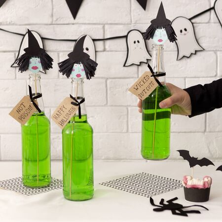 Choose your witch. Woman holding halloween cocktail in glass bottle over bricks wall background