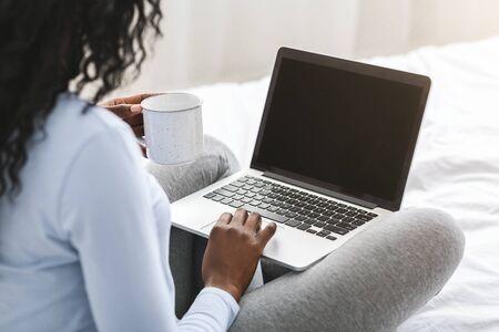 Rückansicht eines afrikanischen Mädchens, das auf einen leeren Laptop-Bildschirm schaut, auf dem Bett sitzt, Tee trinkt, abgeschnitten