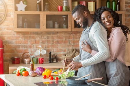 Grateful african american wife embracing her husband from behind at kitchen, making dinner together, copy space