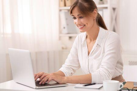 Sorridente imprenditrice utilizzando laptop lavorando in un ufficio moderno. Concetto di carriera di successo Archivio Fotografico