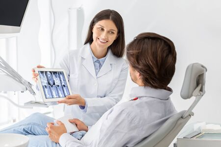Beautiful female dentist doctor showing his patient x-ray results on tablet, free space