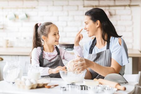 Playful mother and daughter having fun in kitchen while kneading dough for cookies