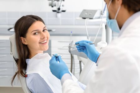 Happy woman making check up in modern dental office, doctor checking her teeth, side view, empty space