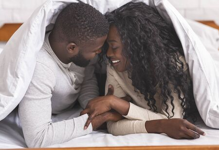 Romantic african american couple resting on bed under blanket, enjoying weekend together.