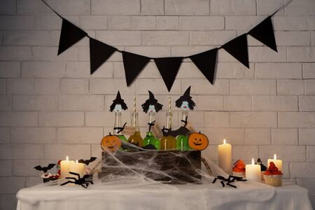Halloween romantic party. Green witches cocktails and cupcakes over white bricks wall with candles