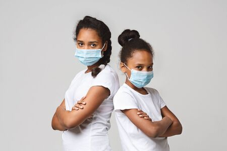 Two young sisters wearing medical masks over grey studio