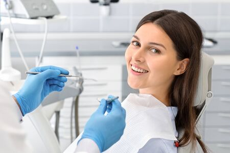 Young happy lady sitting in dentist chair, making regular check up in modern clinic, close up, free space Stock Photo