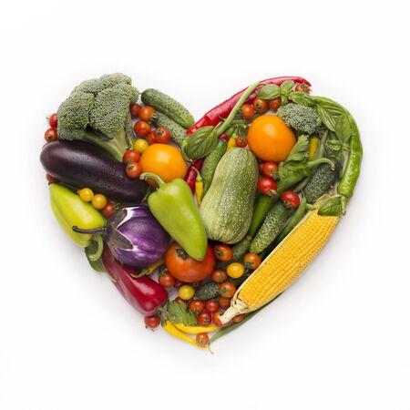 Healty diet concept. Heart shape frame of fresh vegetables on white background