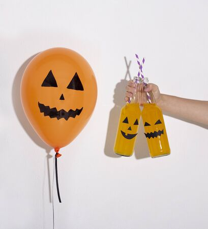 Creative Halloween balloon planning to drink party cocktails on white background Stock Photo