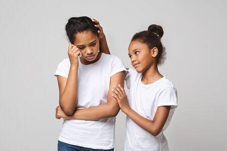 Klein zwart meisje troost haar overstuur vriendin of zus over grijze studio