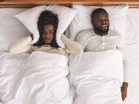 Snoring husband. Unhappy black woman covering her ears with pillow, can not handle loud snore of her partner, top view Banque d'images - 131815923