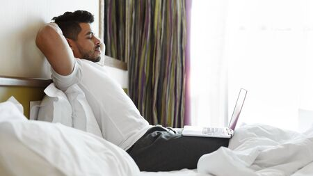 Relaxed handsome eastern man listening to music in bed, leaning back, using laptop, panorama with copy space