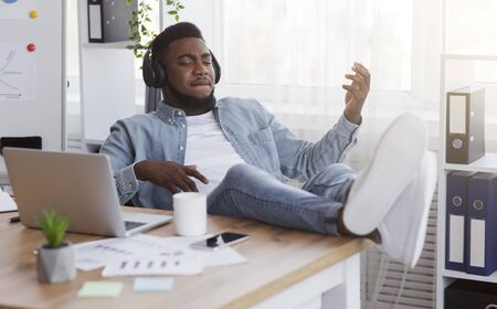 Hidden talents. Handsome african american guy listening music in headphones at workplace and playing virtual guitar, relaxing in office.
