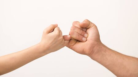 Friendship concept. Father and daughter hand making promise holding little fingers, isolated on white background