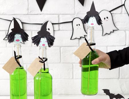 Close up of conceptual and creative green Halloween drinks with witches heads over white bricks wall background Zdjęcie Seryjne