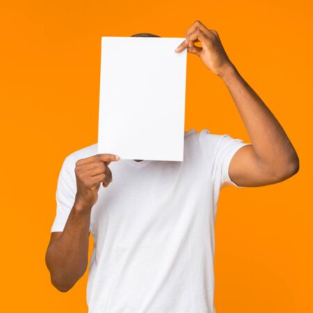 Unrecognizable Black Man Covering Face With Clean Paper Sheet Standing Over Orange Studio