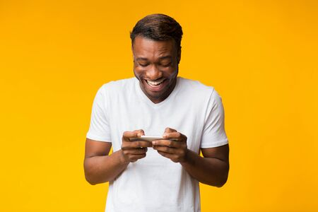 Mobile Gaming. Excited Black Man Using Cellphone Playing Online Games Standing Over Yellow