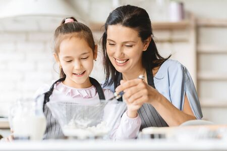 Family recipes. Mother teaching small daughter how to make dough, sharing her experience
