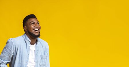 Awesome sales. Ecstatic african american guy looking up at copy space with amazement, isolated on yellow Imagens