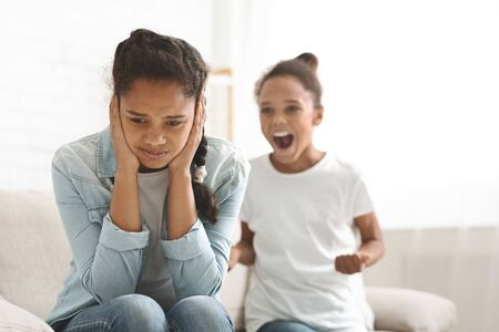 Bad behaviour. Hysterical black girl yelling at her older sister at home, copy space Imagens