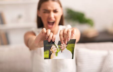 Divorce. Angry Woman Ripping Wedding Photo With Ex-Husband After Breakup Indoor. Selective Focus