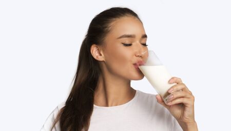 Dairy Products. Young Woman Drinking Milk From Glass Standing Over White Studio Фото со стока