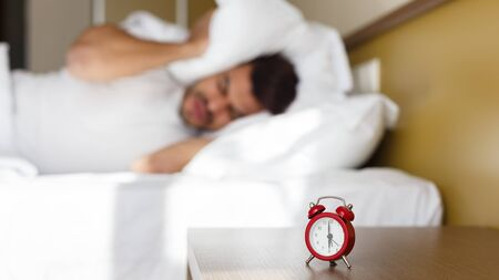 Exhausted eastern man being awaken alarm clock in his bedroom, covering head with pillow, copy space, panorama