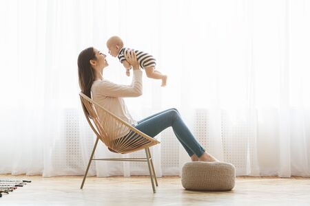 Lets fly. Beautiful mom lifting her adorable newborn child up in the air while sitting in modern woven chair, relaxing at home together, copy space Reklamní fotografie