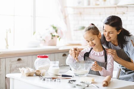 Happy family of mother and daughter making dough together, mixing ingredients in bowl on kitchen table, copy space