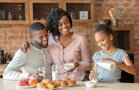 Vitamins and minerals. Beautiful black family having breakfast together, girl pouring milk, copy space Фото со стока