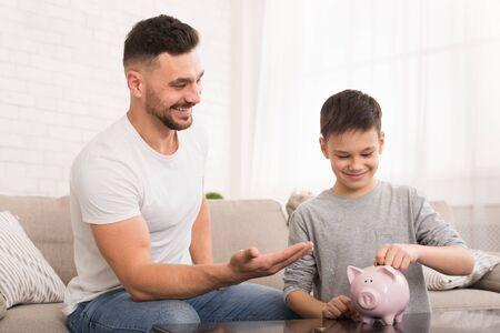 Financial education. Dad teaching his son to save money, boy putting coins into piggy bank, free space