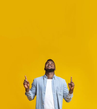 Look there. Handsome african american guy pointing upwards at copy space on yellow studio background.