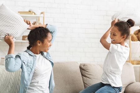 Pillow fight. Two adorable african girls having fun at home, copy space Stok Fotoğraf