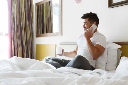 Young eastern guy sitting in hotel bed, talking by phone and drinking coffee, empty space Фото со стока