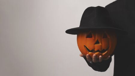 Jack o Lantern holding his pumpkin head with hat in hand over gray background, panorama, copy space