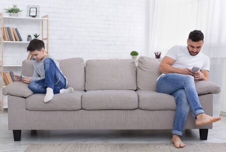 Focused on devices. Teen boy and his father carried away with mobile phones, sitting on other sides of couch, ignoring each other at home, empty space