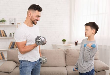 Living healthy life. Happy father and son exercising with dumbbells at home, free space