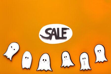 Nightmare sales. Happy smiling ghosts dancing on orange Halloween banner