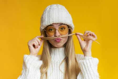 Smiling girl with sunglasses and winter hat making funny mustache out of her hair, yellow 版權商用圖片