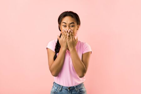 Shocked woman covering her mouth with hands looking at camera, pink