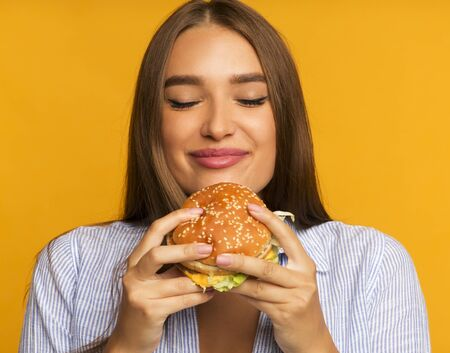 Cheat Meal. Happy Girl Eating Burger Standing Over Yellow