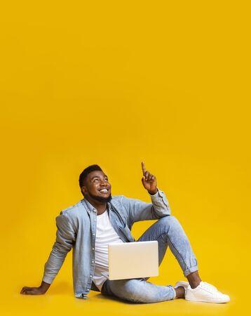 Grande offre. Un homme noir du millénaire assis sur le sol avec un ordinateur portable et pointant vers le haut sur l'espace de copie sur jaune Banque d'images
